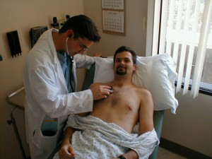 physician assistant auscultating a patient's heart